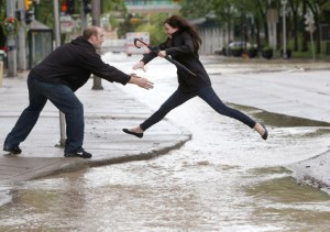 CALGARY, ALBERTA.:  JUNE 21, 2013 --  Blake Wartenbe catches his wife Desiree as she jumps over flowing water in a flooded downtown Calgary, Alberta on June 21, 2013. For City story by ? (Leah Hennel/Calgary Herald)